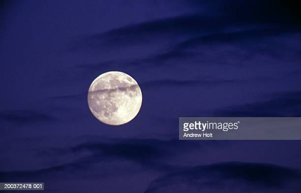 Full moon behind streaky dark clouds, night