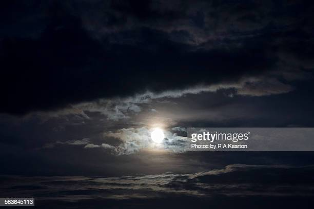 Full moon between bands of silvery cloud