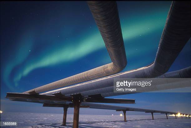 A full moon helps illuminate the Alaskan pipeline under the faint glow of the Aurora Borealis November 19 2002 near Milne Point Alaska Smaller oil...