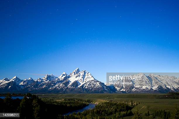 A full moon illuminates Grand Teton National Park with stars in the sky at the Snake River Overlook in Grand Teton National Park, Wyoming.