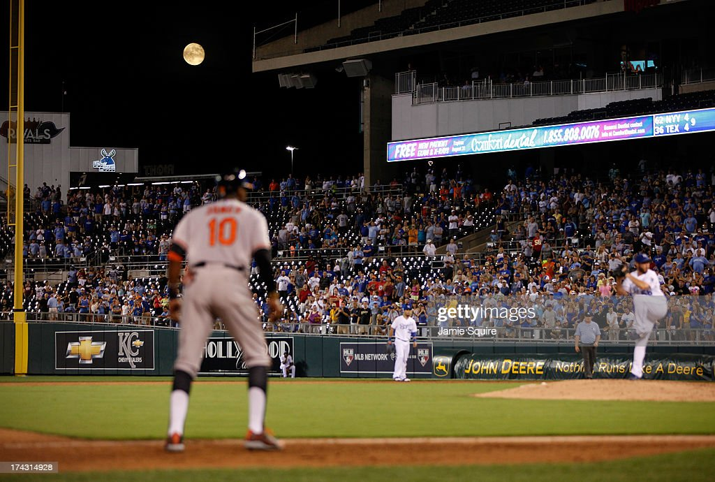 A full moon looms over the field as Adam Jones #10 of the Baltimore Orioles on third watches a pitch by Greg Holland #56 of the Kansas City Royals during the game at Kauffman Stadium on July 23, 2013 in Kansas City, Missouri.