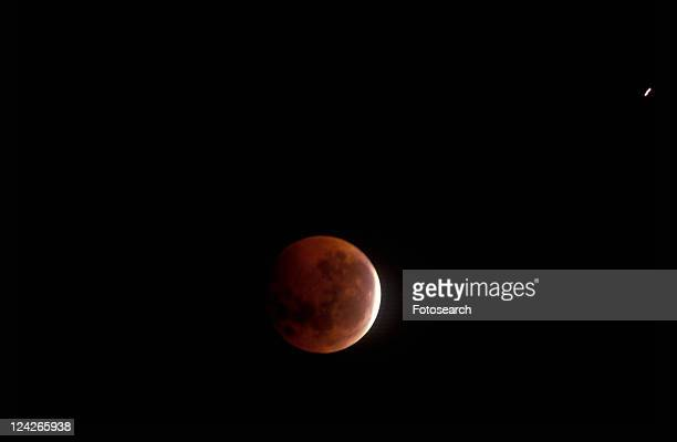 A full moon mostly covered by Earth's shadow during a lunar eclipse against a black starless sky