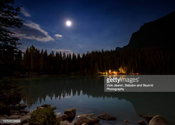 full moon, night sky and boathouse at lake louise, canada - lake louise lake stock photos and pictures