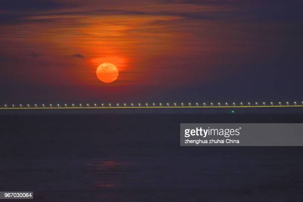 A Full Moon On Sea Over Bridge