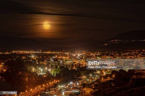 full moon over city - harvest moon stock pictures, royalty-free photos & images