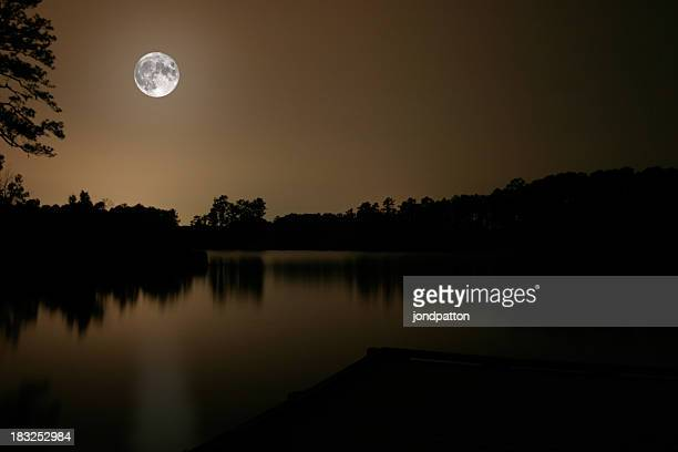 Full moon over lake giving reflection to surrounding trees
