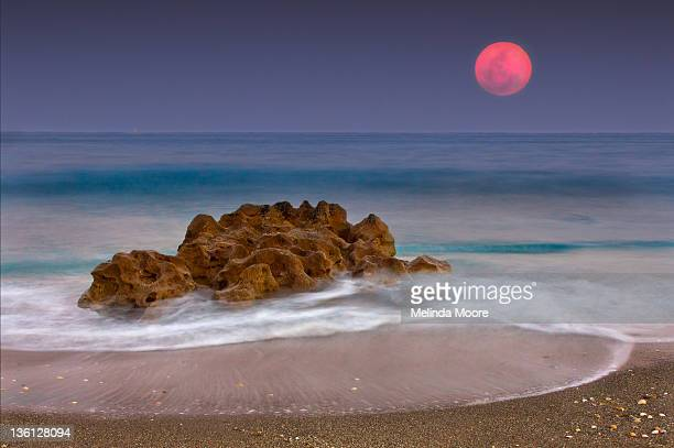 Full moon over ocean and rocks