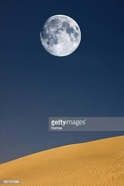 full moon over sand dunes