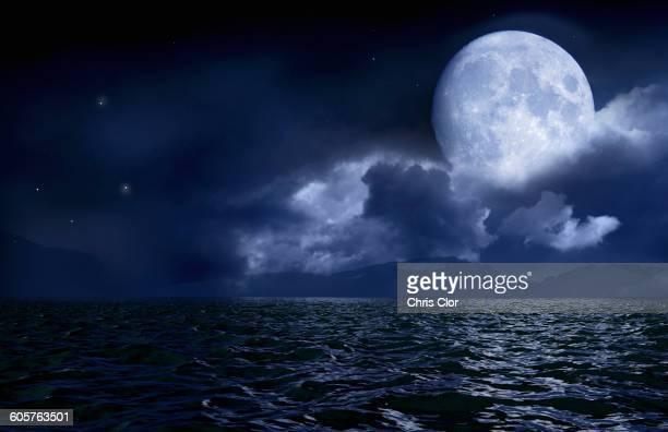 full moon over seascape and horizon - luna llena fotografías e imágenes de stock