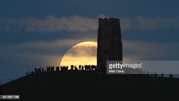 A full moon rises behind Glastonbury Tor as people gather to celebrate the summer solstice on June 20 2016 in Somerset England Tonight's strawberry...