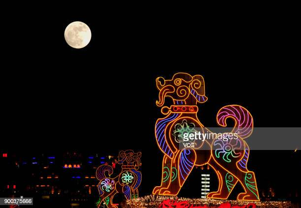 A full moon rises over a dog shaped light on New Year's Day on January 1 2018 in Dalian Liaoning Province of China
