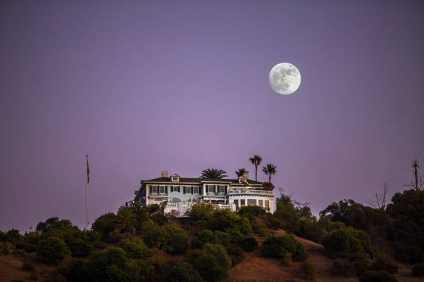 A full moon rises over Catalina Island's Avalon Harbor. The Wrigley Mansion is in the foreground.