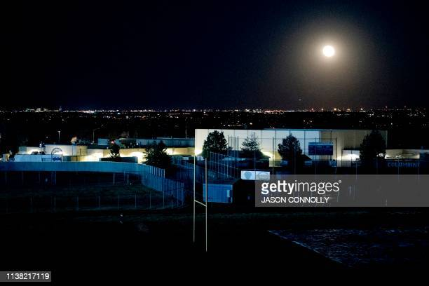 A full moon rises over Columbine High School in Littleton Colorado on April 19 2019 The Columbine community was gathering at Clement Park to honor...