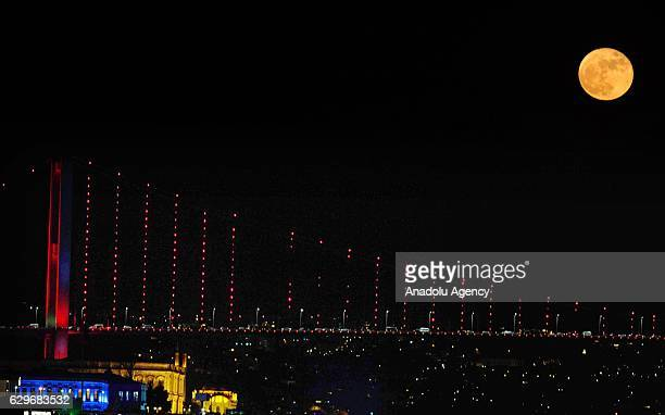 Full moon rises over the 15 July Martyrs Bridge which is also known as Bosphorus Bridge in Istanbul Turkey on December 14 2016