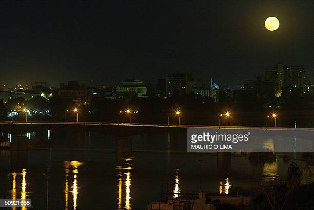 A full moon rises over the city of Baghdad and a lit bridge over the Tigris River in the early evening of 03 June 2004 Residents of the city are...