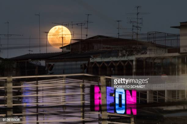 TOPSHOT A full moon rises over the horizon above residential and commercial buildings in Bangkok on January 31 2018 Skywatchers were hoping for a...