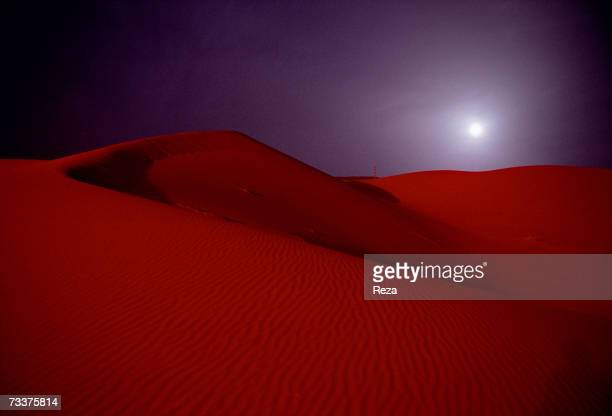 A full moon rises over the red sand dunes just outside the Saudi Aramco oil field complex facilities at Shaybah in the Rub' al Khali desert on March...