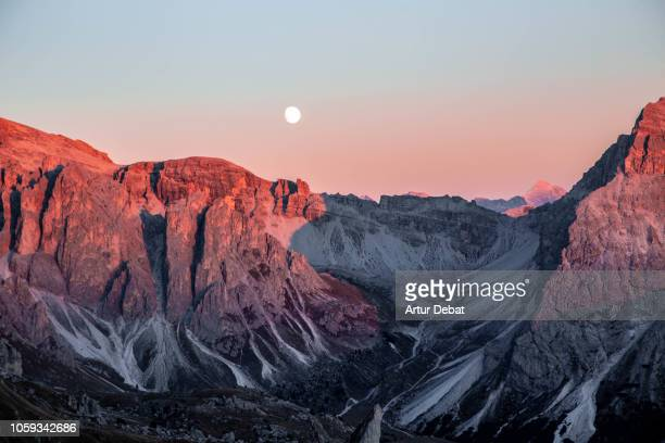 Full moon rising above the Dolomites Italian Alps during the sunset in Seceda summits.