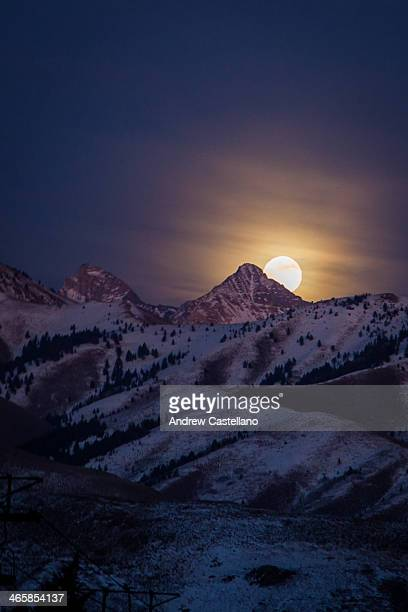 full moon rising behind snowy mountain peak - sun valley idaho stock photos and pictures