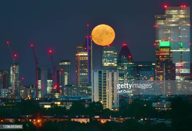 Full moon rising over the City of London skyline, England, 5th July 2020.