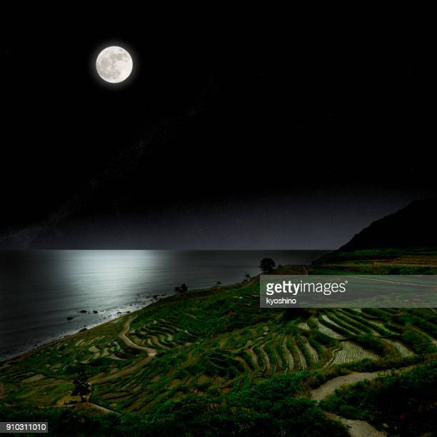full moon rising over the rice terrace fields - hokuriku region stock photos and pictures