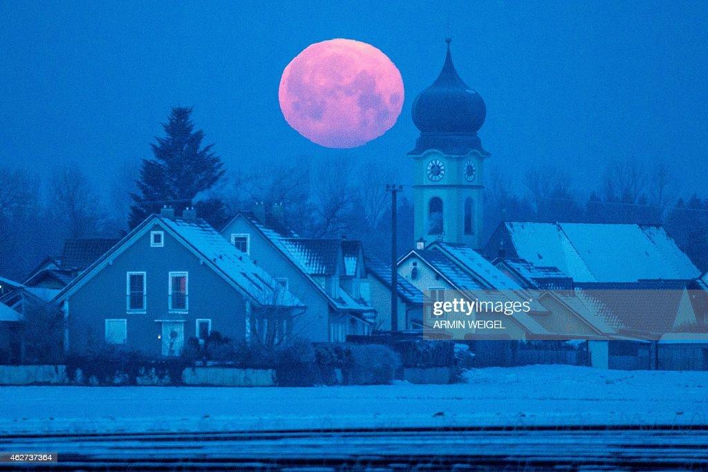 Full moon sets behind the parish church of Schoenach near Regensburg, southern Germany, on February 4, 2015.