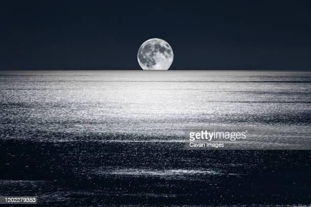 full moon sets over the mediterranean - 密造酒 ストックフォトと画像
