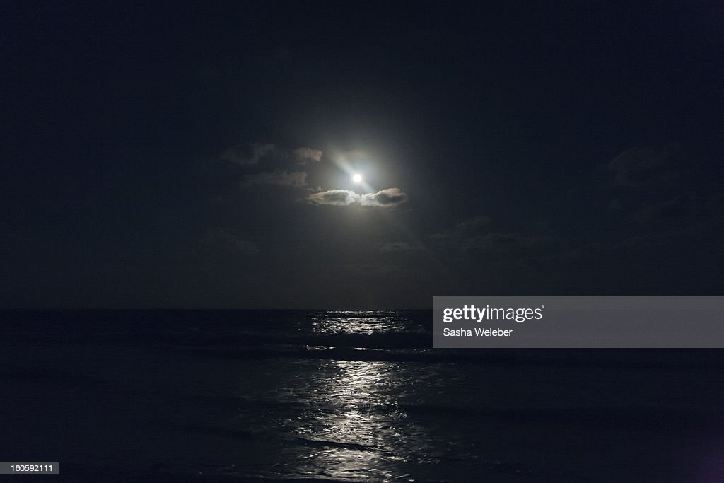 full-moon-through-clouds-over-the-ocean-picture-id160592111