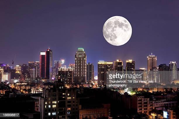 full moon upon lights of city - luna llena fotografías e imágenes de stock