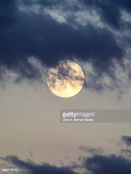 Full moon with a blue sky with clouds to the late afternoon