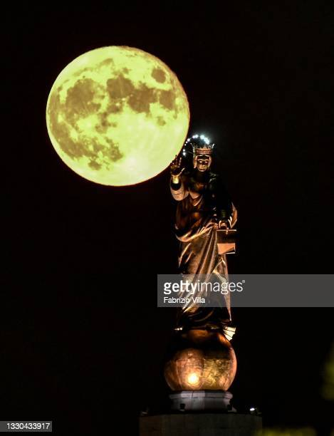 """Full moon with the Madonnina of the Strait of Messina. Sicily on July 24, 2021 in Messina, Italy. The statue of """"Madonna della Lettera"""" is erected at..."""