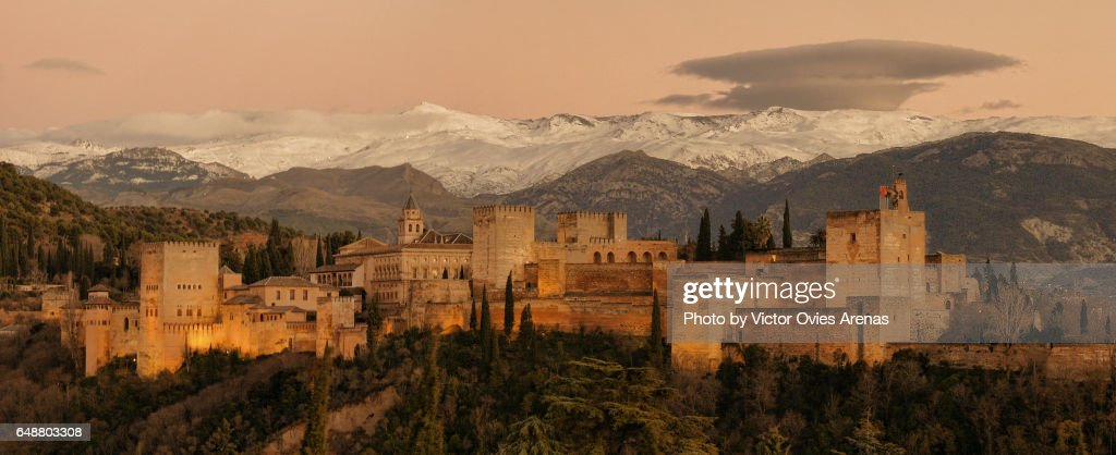Full panoramic view of the Alhambra illuminated and the Sierra Nevada mountain range at twilight from the Albaicin in Granada, Andalusia, Spain : Foto de stock