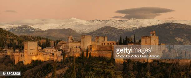 Full panoramic view of the Alhambra illuminated and the Sierra Nevada mountain range at twilight from the Albaicin in Granada, Andalusia, Spain