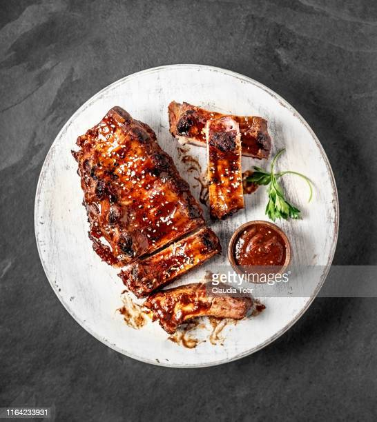 full rack of grilled barbecue ribs with barbecue sauce on cutting board on black background - barbeque sauce stock photos and pictures