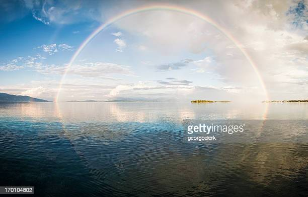 full rainbow over the sea - rainbow stock pictures, royalty-free photos & images