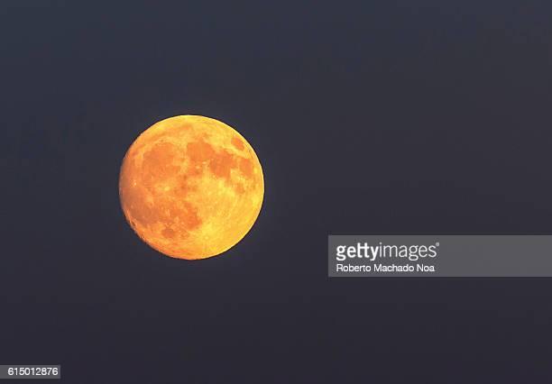 Full redish beautiful full moon As Autumn season advances daytime become shorter