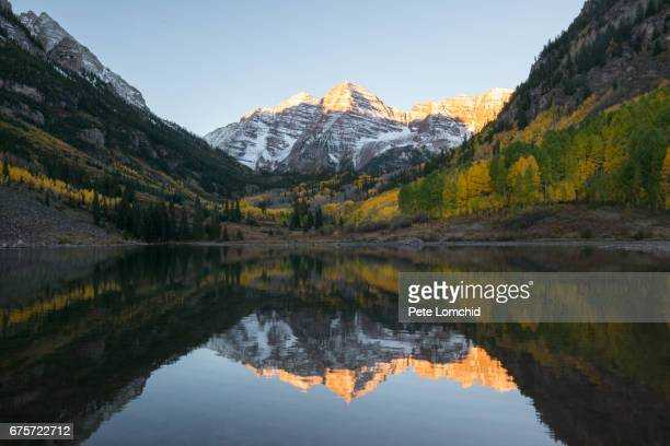 full reflection of maroon bells autumn, colorado - maroon bells stock photos and pictures