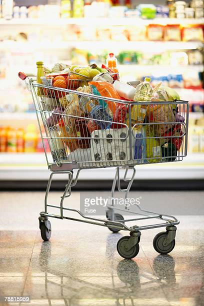 full shopping cart in grocery store - caddie rempli photos et images de collection