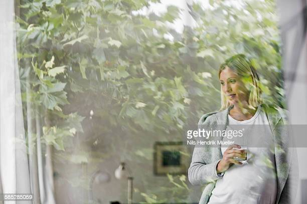 Full term pregnancy young woman at home behind window