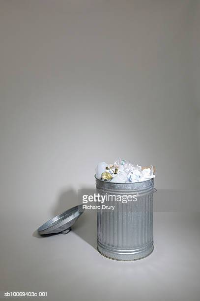 full trash can with lid lying beside, studio show - richard drury stock pictures, royalty-free photos & images