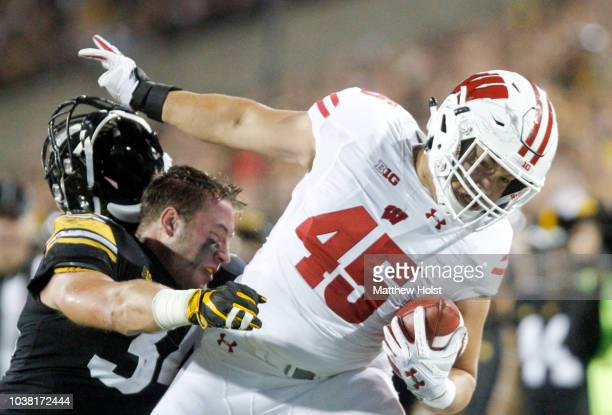 Fullback Alec Ingold of the Wisconsin Badgers breaks a tackle in the first half by linebacker Kristian Welch of the Iowa Hawkeyes on September 22,...