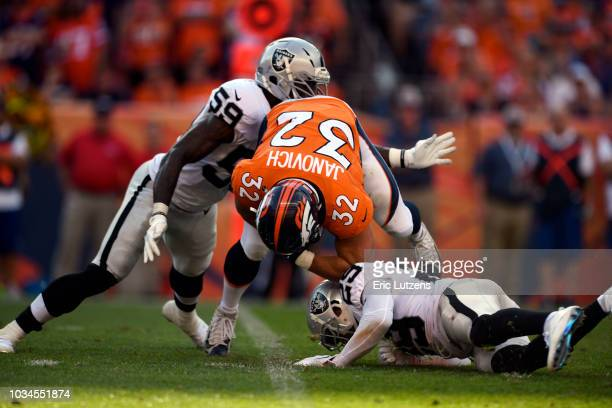 fullback Andy Janovich of the Denver Broncos gets taken down by linebacker Tahir Whitehead of the Oakland Raiders and defensive back Leon Hall of the...