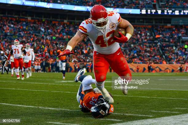 Fullback Anthony Sherman of the Kansas City Chiefs is hit by cornerback Marcus Rios of the Denver Broncos at Sports Authority Field at Mile High on...