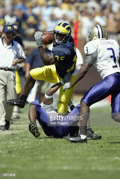Fullback BJ Askew of Michigan leaps over a defender as he runs with the ball during the NCAA football game against the Washington Huskies at Michigan...