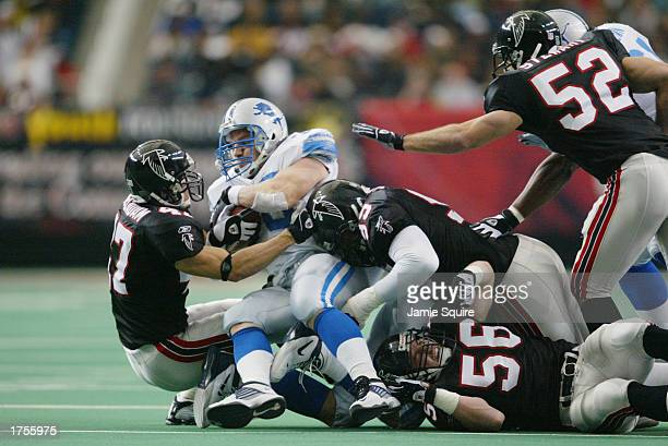 Fullback Corey Schlesinger of the Detroit Lions is tackled by the Atlanta Falcons defense during the first half of the game at the Georgia Dome on...