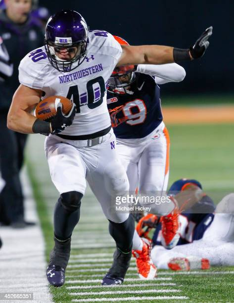 Fullback Dan Vitale of the Northwestern Wildcats runs the ball after a reception as defensive back Earnest Thomas III of the Illinois Fighting Illini...