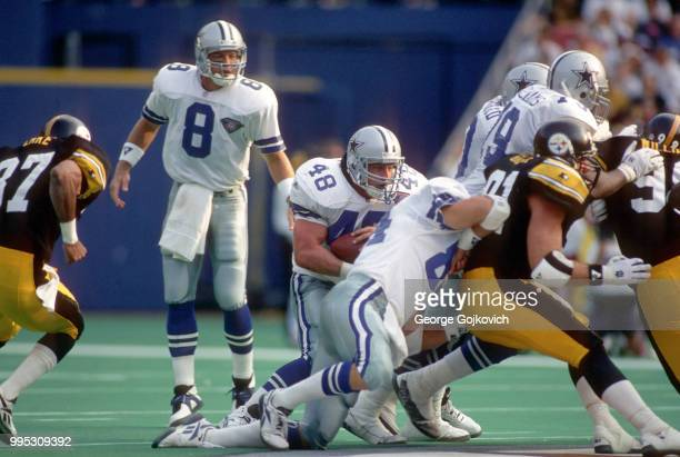 Fullback Daryl Johnston of the Dallas Cowboys runs with the football behind the blocking of tight end Jay Novacek after taking a handoff from...