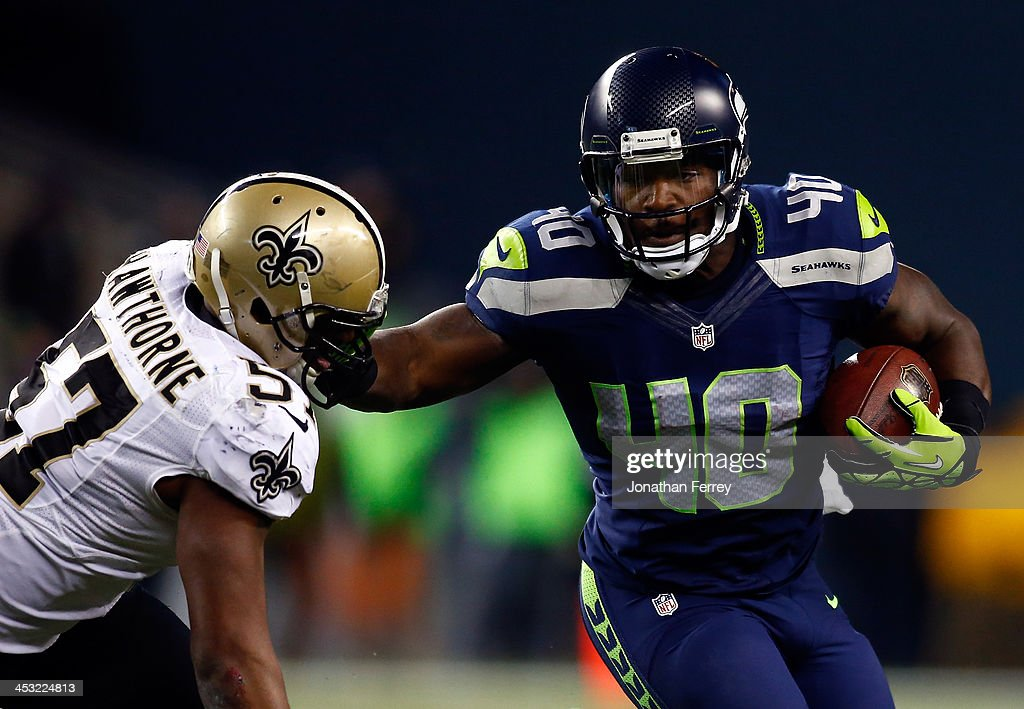 Fullback Derrick Coleman #40 of the Seattle Seahawks carries the ball as outside linebacker David Hawthorne #57 of the New Orleans Saints defends during a game at CenturyLink Field on December 2, 2013 in Seattle, Washington.