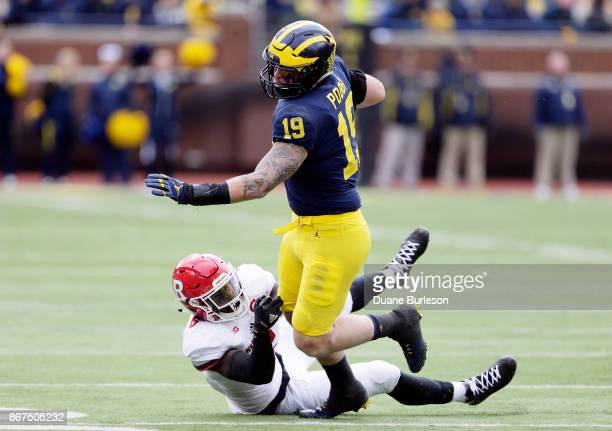 Fullback Henry Poggi of the Michigan Wolverines avoids linebacker Deonte Roberts of the Rutgers Scarlet Knights while carrying the ball during the...