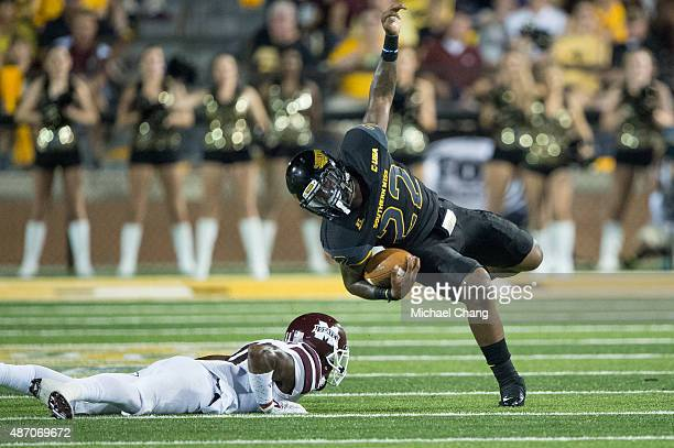 Fullback Jay'Shawn Washington of the Southern Miss Golden Eagles spins to avoid a tackle by defensive back Kivon Coman of the Mississippi State...